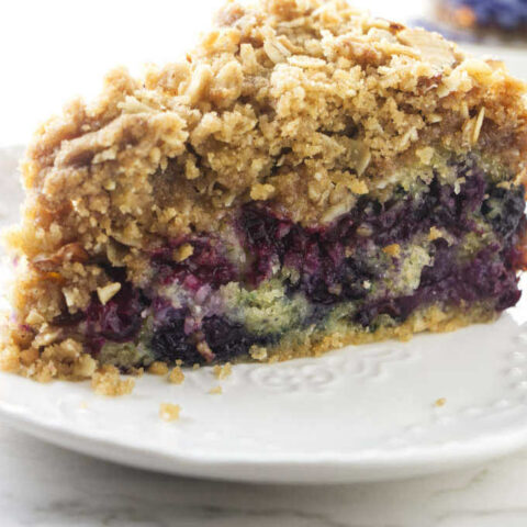 A slice of blueberry buckle coffee cake on a dessert plate.