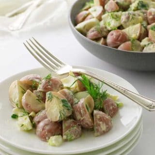 plate of dilly potato salad with a bowl in the background