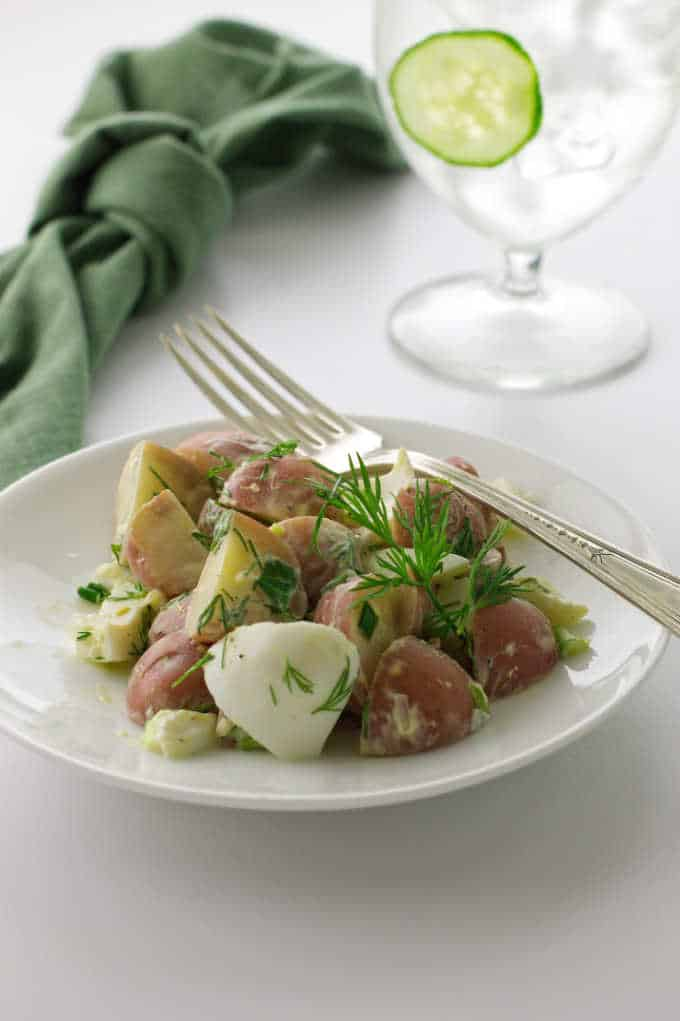 small plate of fresh dill potato salad with a glass in the background