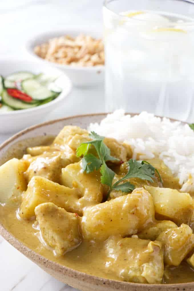 Close up of a bowl of Curry Chicken and Potatoes with salad in the background
