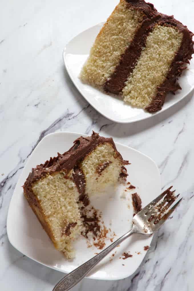 two slices of yellow cake with chocolate frosting