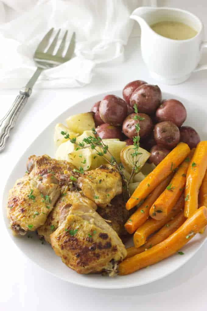 Crockpot Chicken and Vegetables served on a platter with a pitcher of gravy