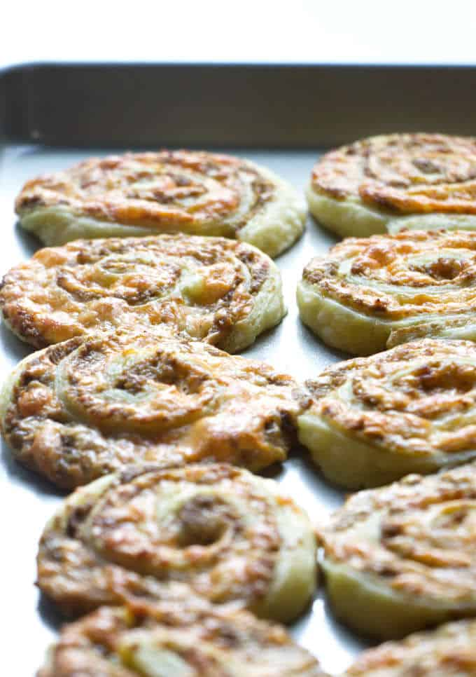 Olive and cheese pinwheel appetizers on a baking sheet