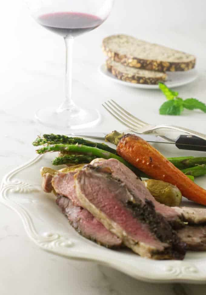 sliced lamb on a plate with vegetables