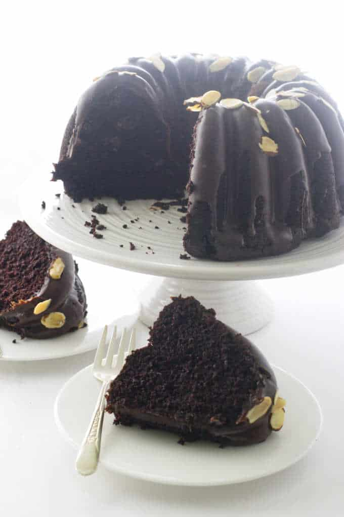 two slices of cake below a bundt cake on a stand
