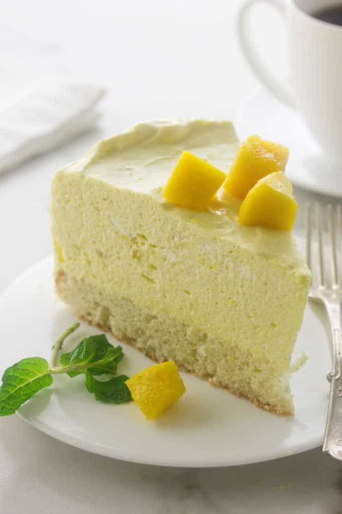 a slice of Mango Mousse Cake and a cup of coffee in the background