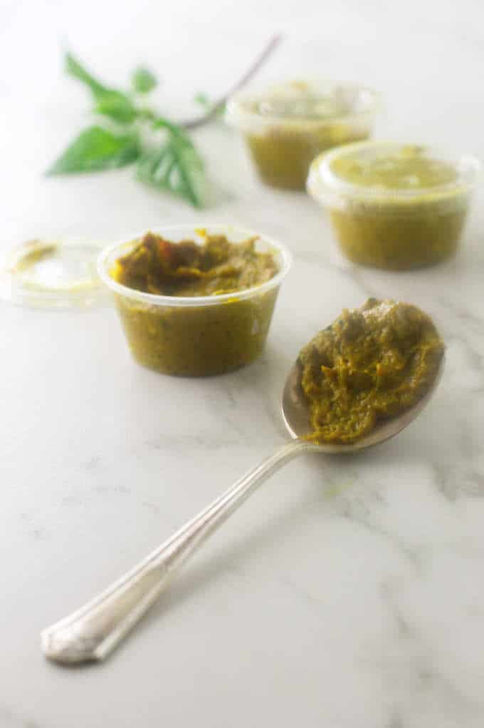 A spoon and three containers of Thai Yellow Curry Paste