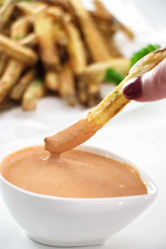 French fry being dipped into fry sauce