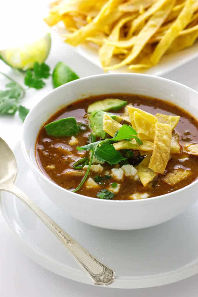 A bowl of chipotle chicken tortilla soup and a plate of tortilla strips