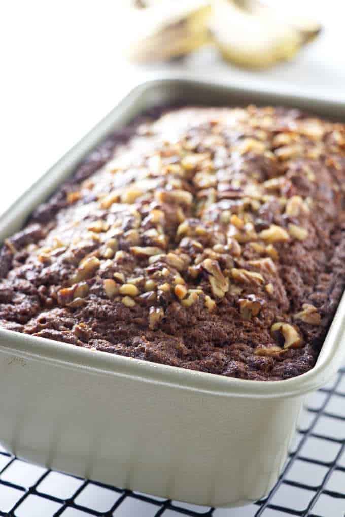 loaf of banana bread in a pan with nuts on top