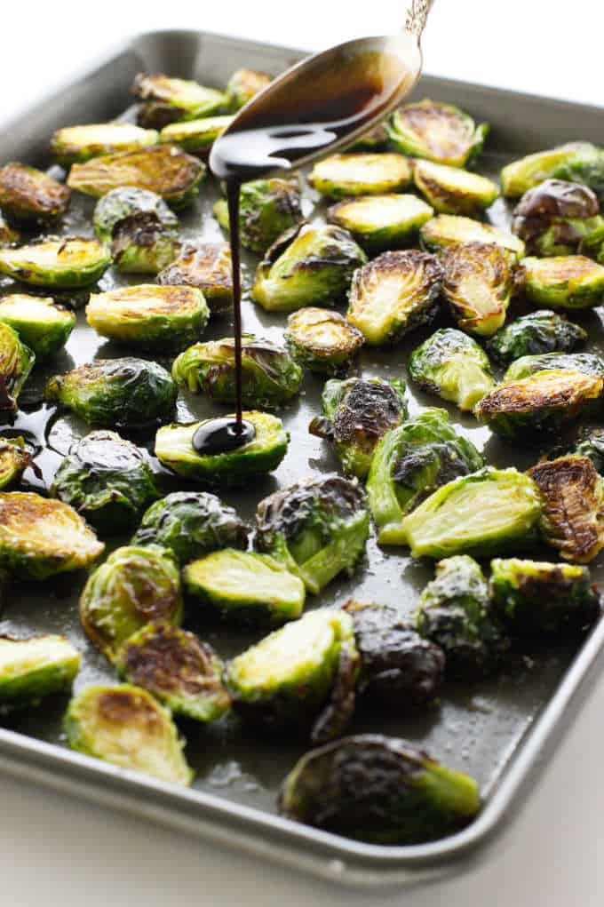 spoon drizzling balsamic on Brussels sprouts