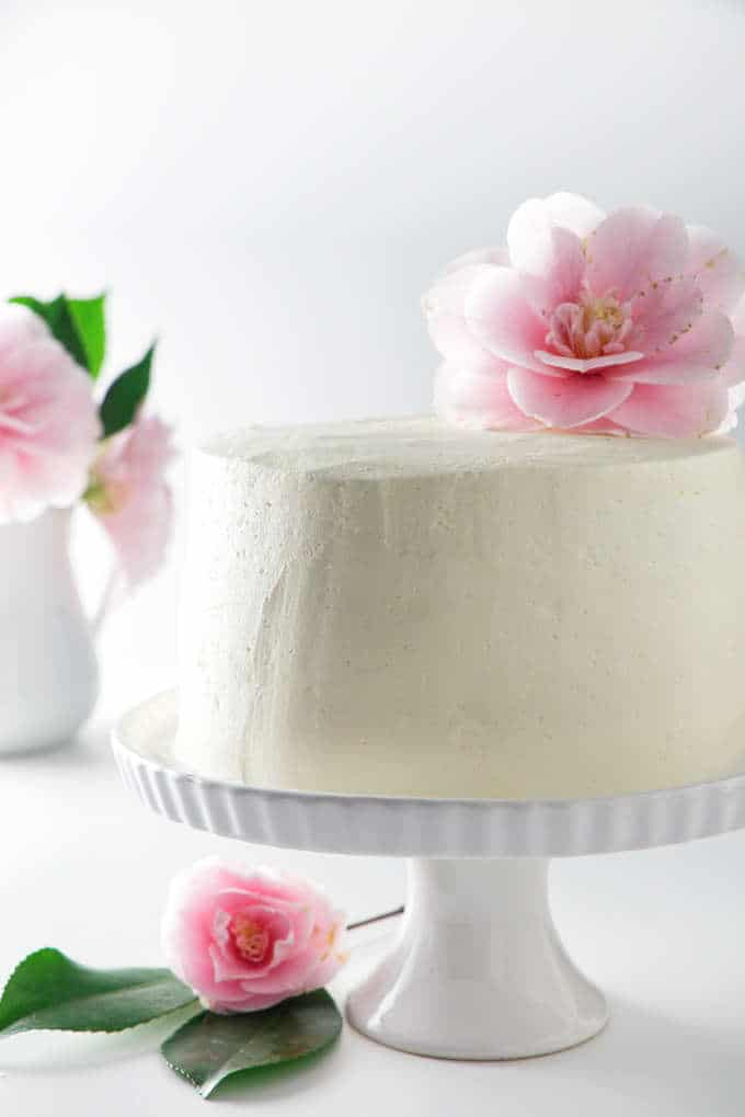 a 6-inch cake on a platter with a flower on top