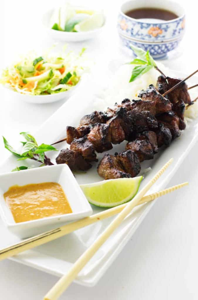 three skewers of pork satay and some peanut sauce