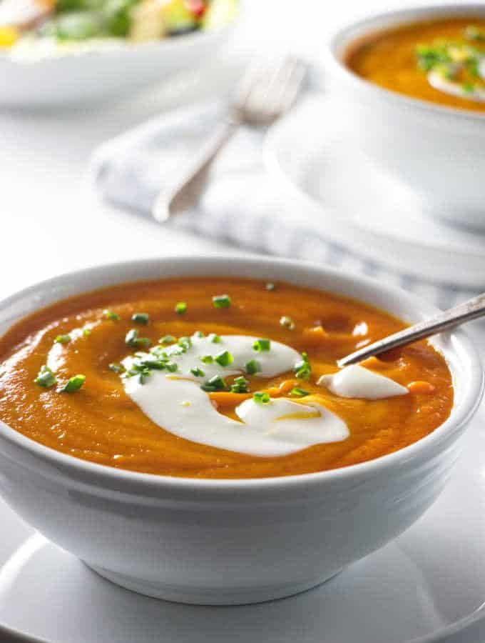 two bowls of soup with salad in the background