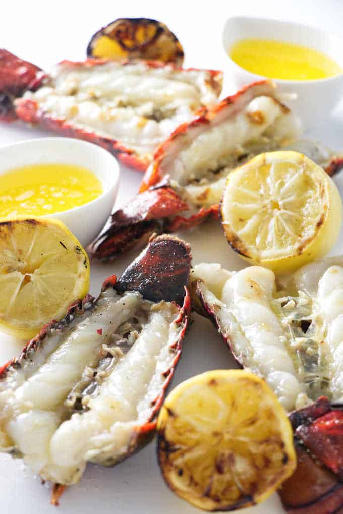 four lobster tails with four grilled lemons