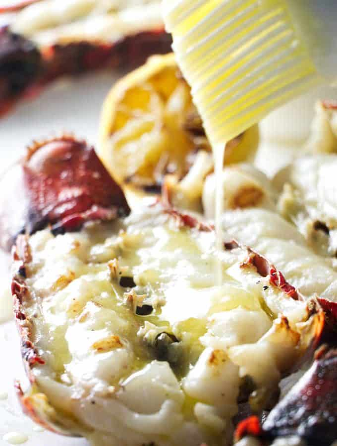 close up of a grilled lobster tail being drizzled with garlic butter sauce