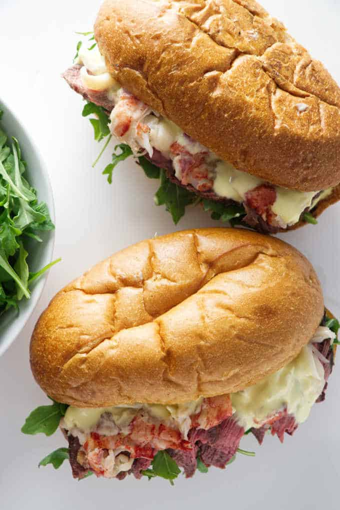 overhead shot of two steak and lobster sandwiches