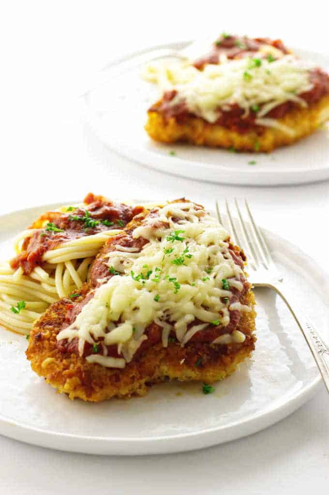 Two plated servings of chicken parmesan with spaghetti