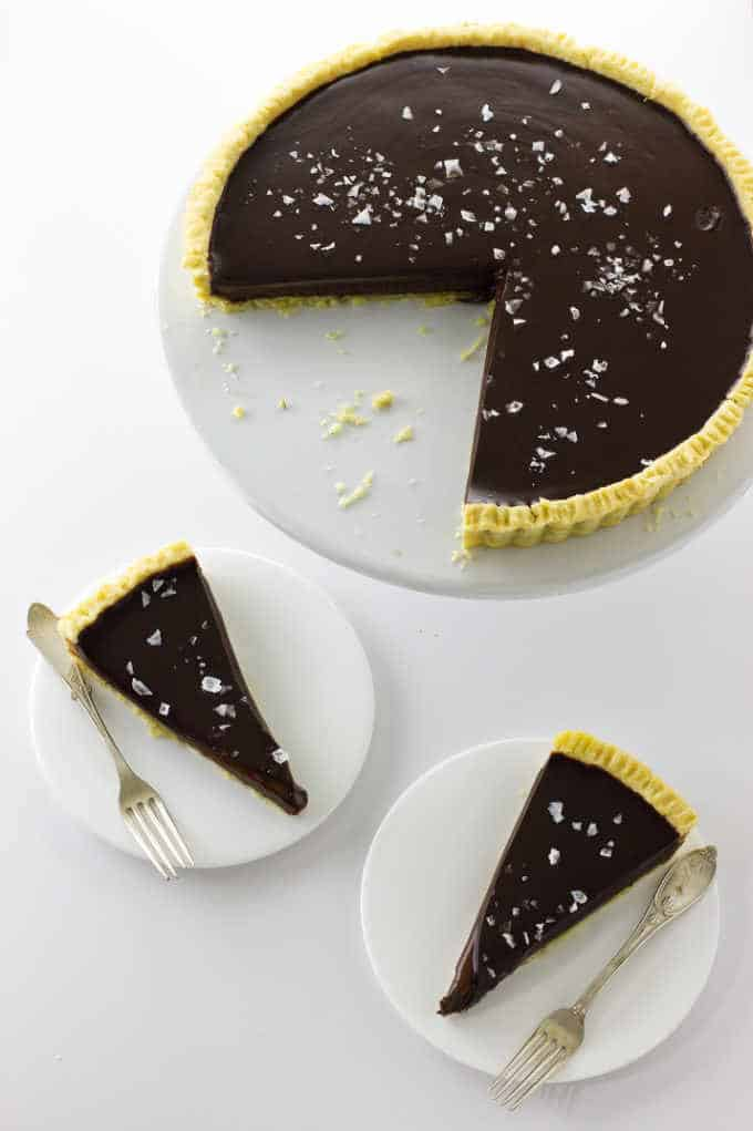 Chocolate Caramel Tart on a cake plate with two slices below on small plates