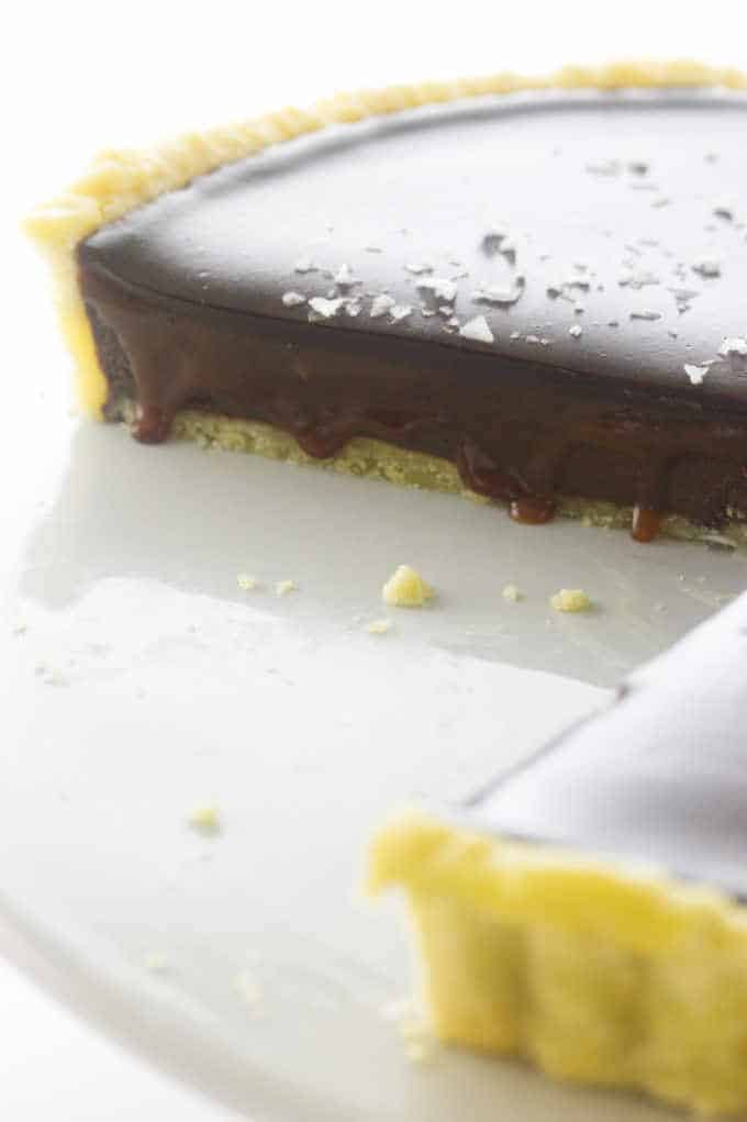 a close-up photo of Chocolate Caramel Tart with the caramel drizzling over the edge