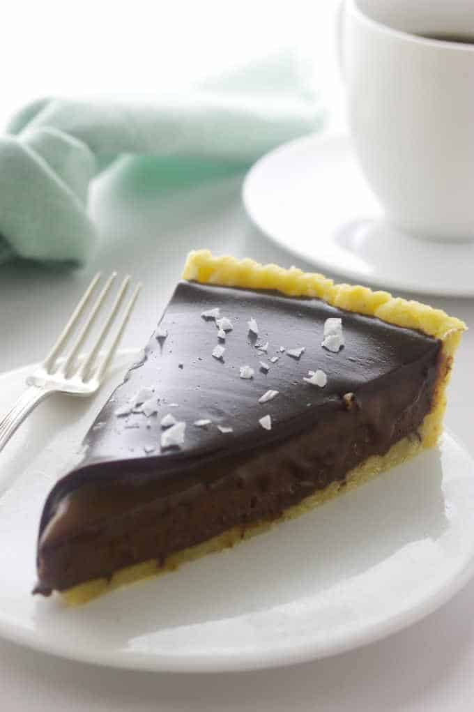a slice of chocolate tart with a cup of coffee in the background