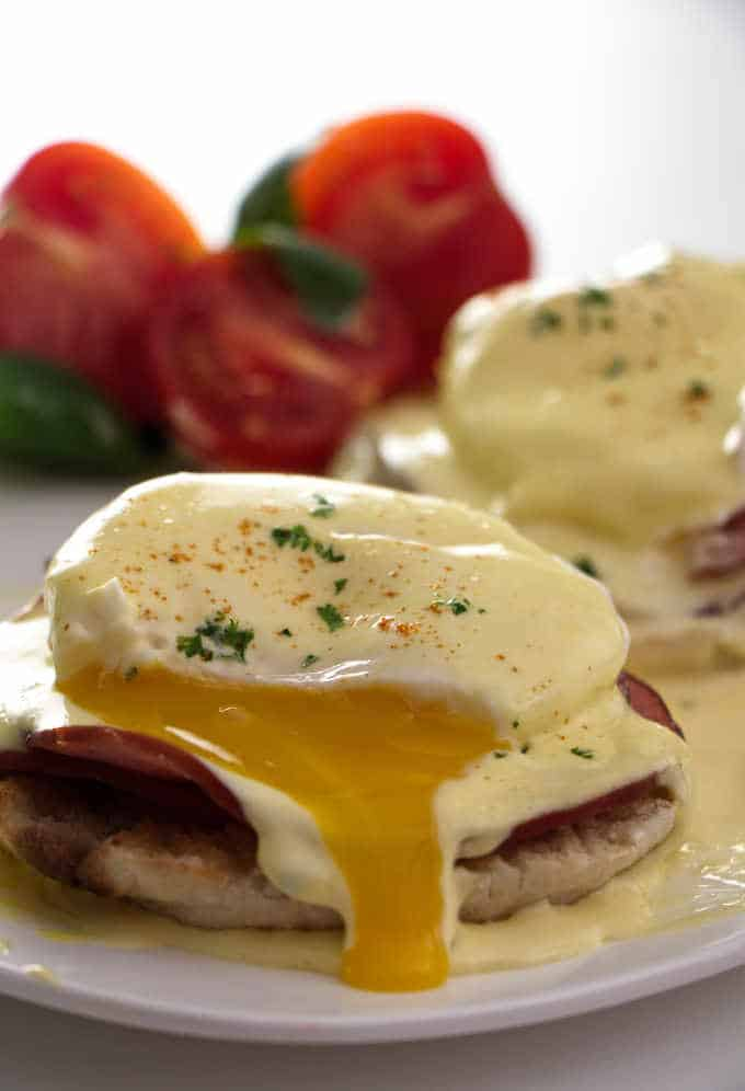 2 eggs Benedicts with tomatoes in the background