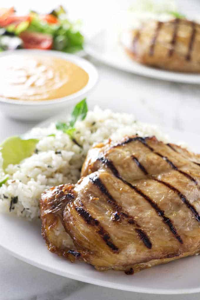 Two plates with grilled chicken breast and a bowl of spicy peanut sauce.