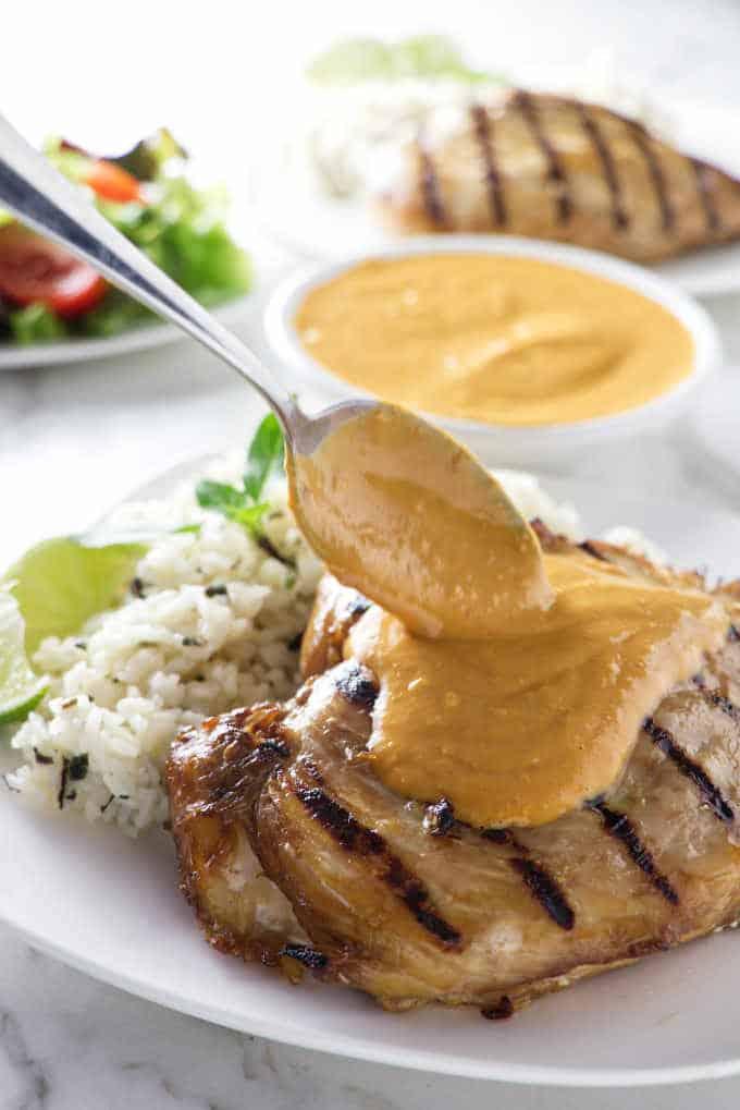 spooning peanut sauce over a chicken breast