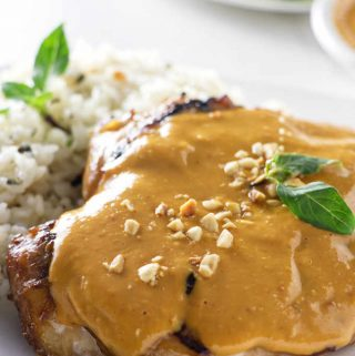 A grilled chicken breast topped with spicy peanut sauce plated with rice.