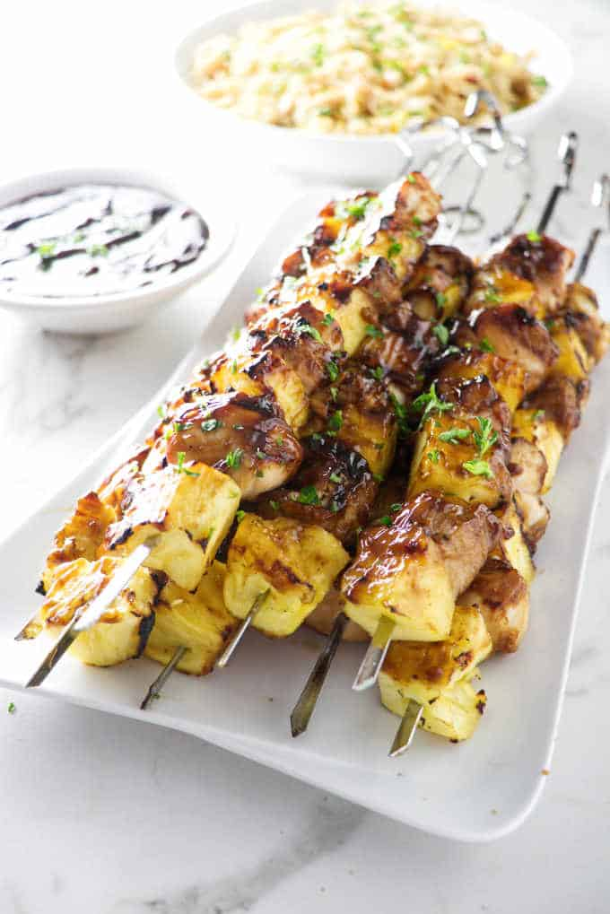 a plate of grilled pineapple chicken kabobs