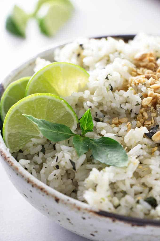 A bowl of basil lime rice with sliced limes in the background
