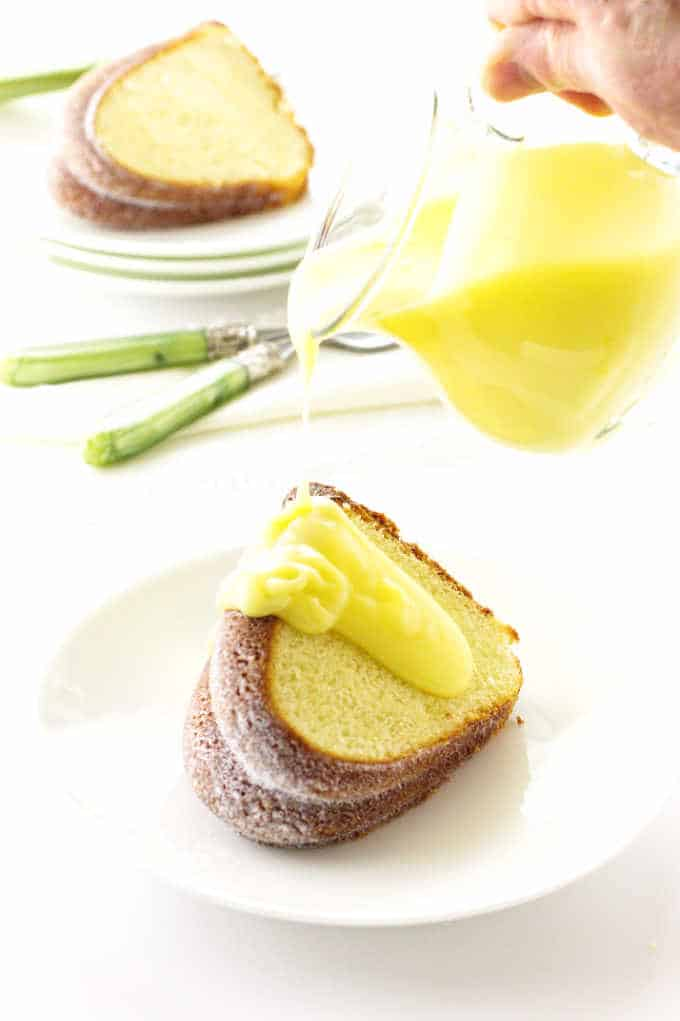A slice of lemon Bundt cake with lemon dessert sauce being poured