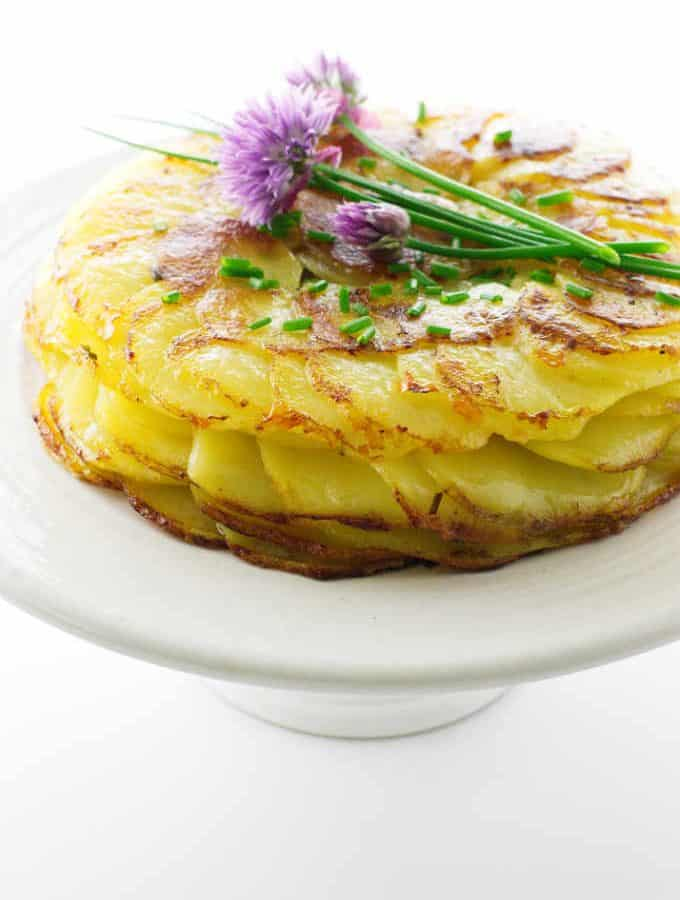 Crisp potatoes Anna on cake pedestal with fresh chive flowers