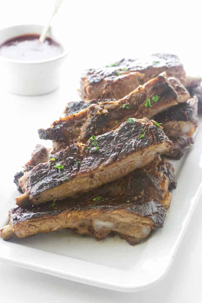 barbecue Ribs on a plate and sauce in the background