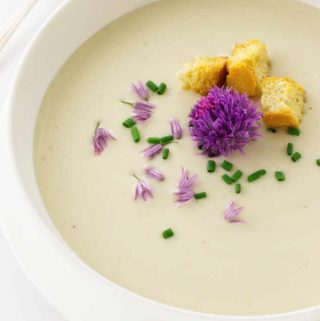 A bowl of soup garnished with chive blossoms, snipped chives and croutons.