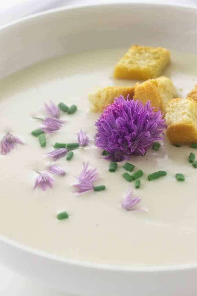 Close up photo of chives, chive blossom and crisp croutons