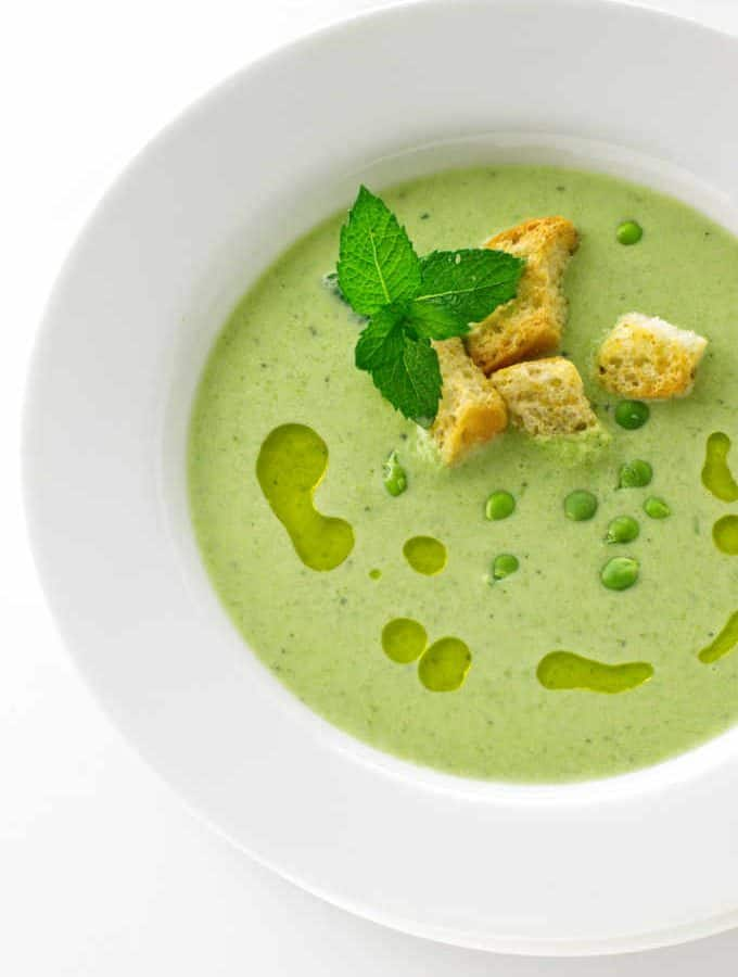 A close up serving of soup garnished with croutons, mint and finishing oil