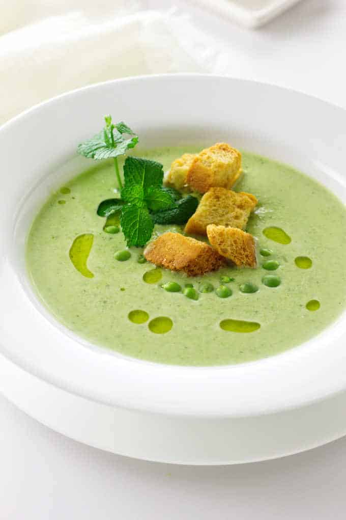 A bowl of fresh green pea soup and mint soup with garnish