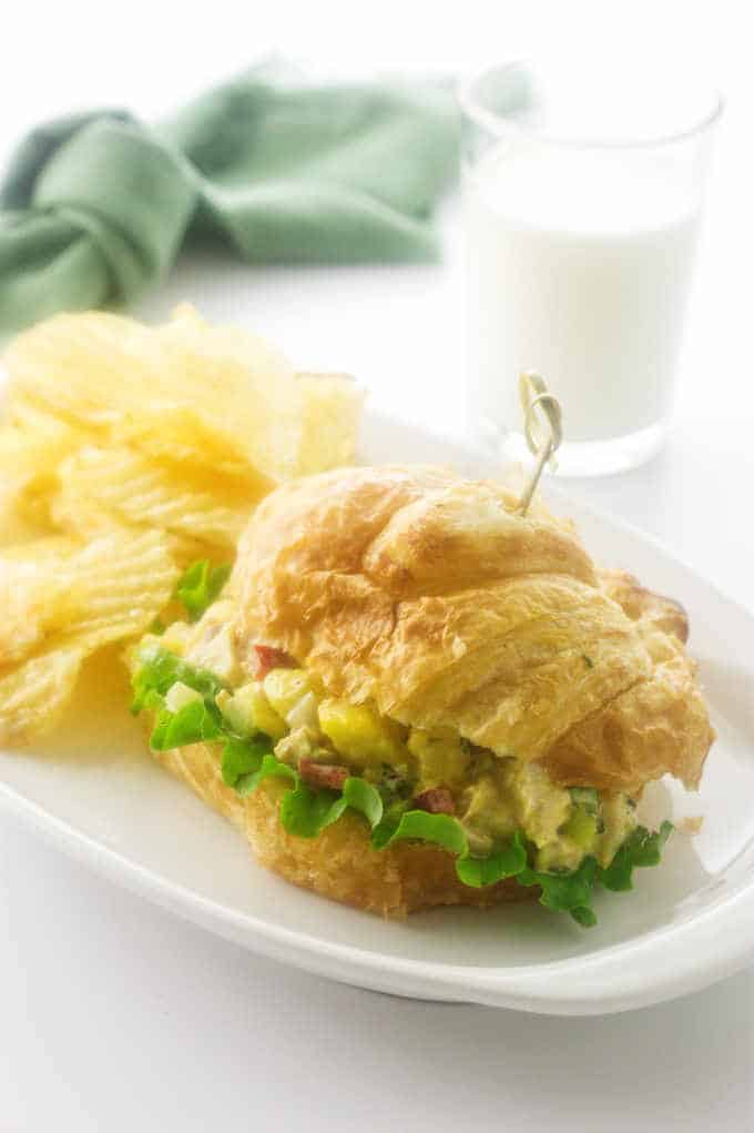 Close up photo of sandwich, chips, milk and napkin