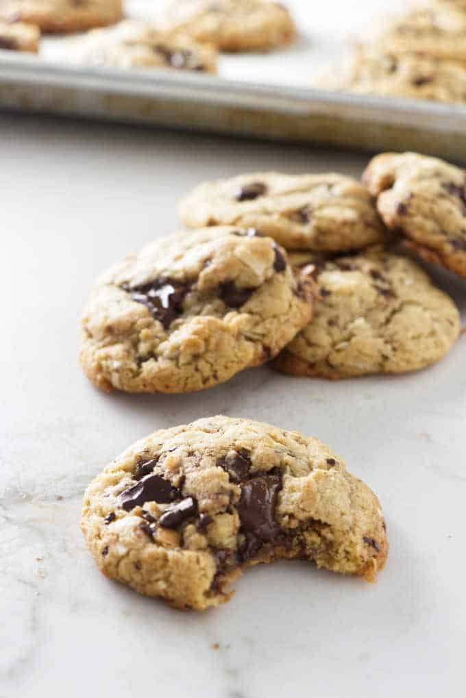 a pile of coconut chocolate chunk tahini cookies with a bite taken from one cookie