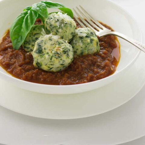 Three malfatti dumplings in tomato sauce.