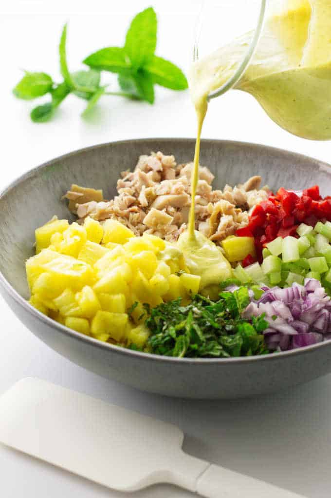 Salad bowl with pineapple-chicken mixture and curry dressing being poured on