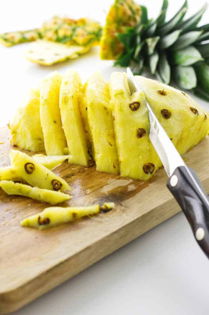 Fresh pineapple with knife removing the eyes