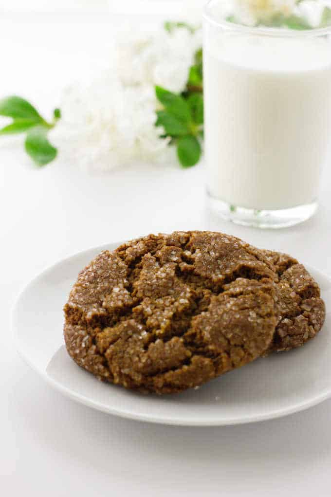Two soft and chewy molasses spice cookies on a plate, glass of milk and flowers in background