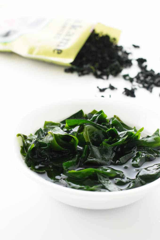 Wakame seaweed soaking in water with bag of dried wakame in background