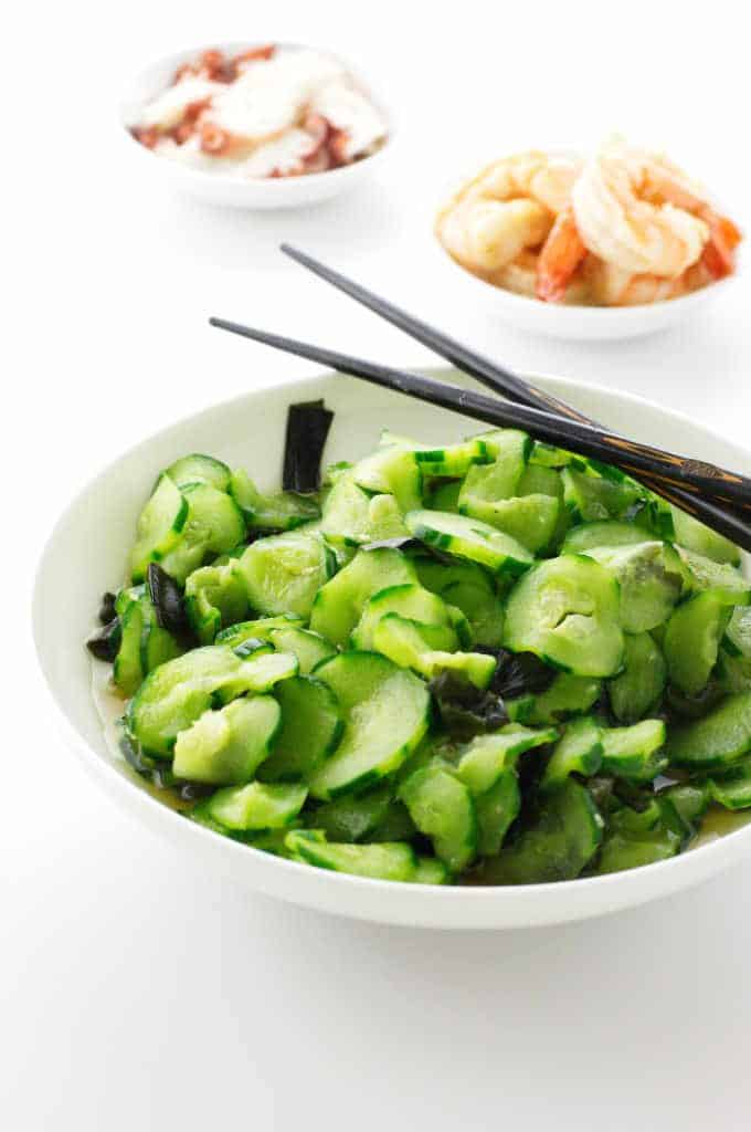 A bowl of cucumber salad and chopsticks. Cooked octopus and shrimp in dishes in background