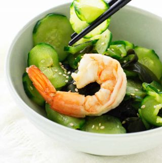 Chopsticks piking up slices of cucumber salad, boiled shrimp on top of salad