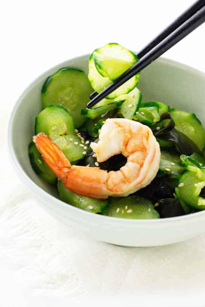 Chopsticks piking up slices of cucumber salad, boiled shrimp on top of salad