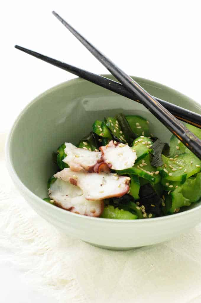 A dish of cucumber salad with sesame seeds and slices of cooked octopus