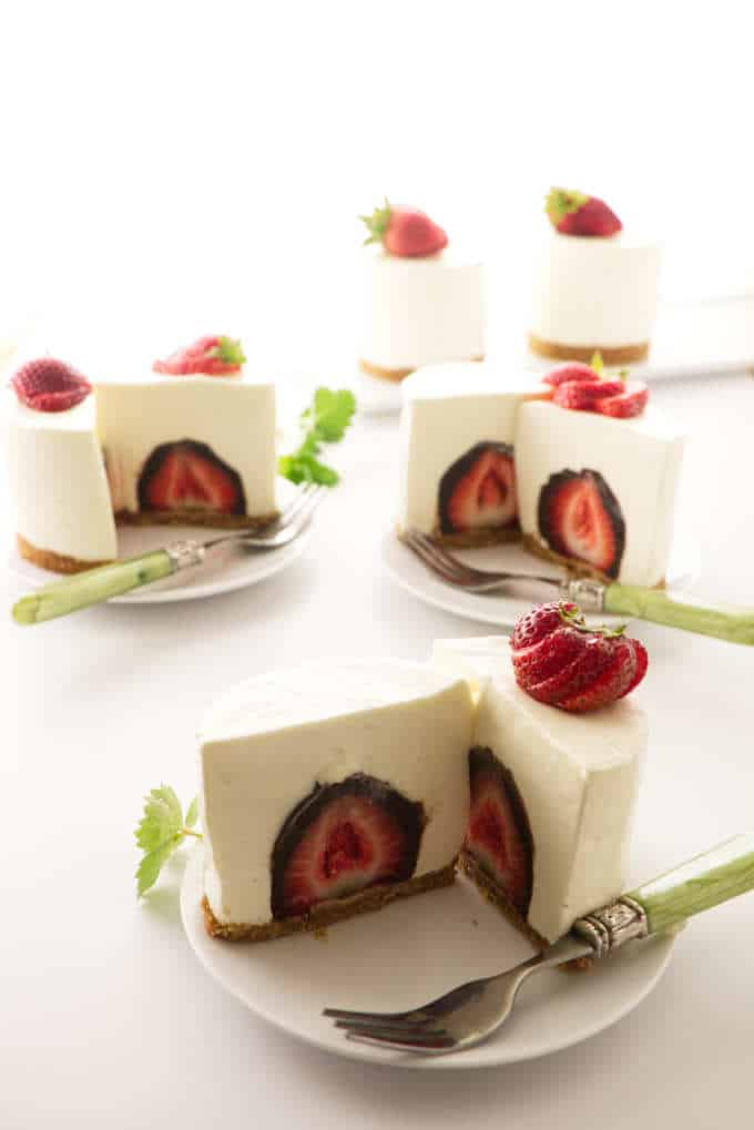 Three individual cheesecakes sliced open in the middle to see a chocolate covered strawberry